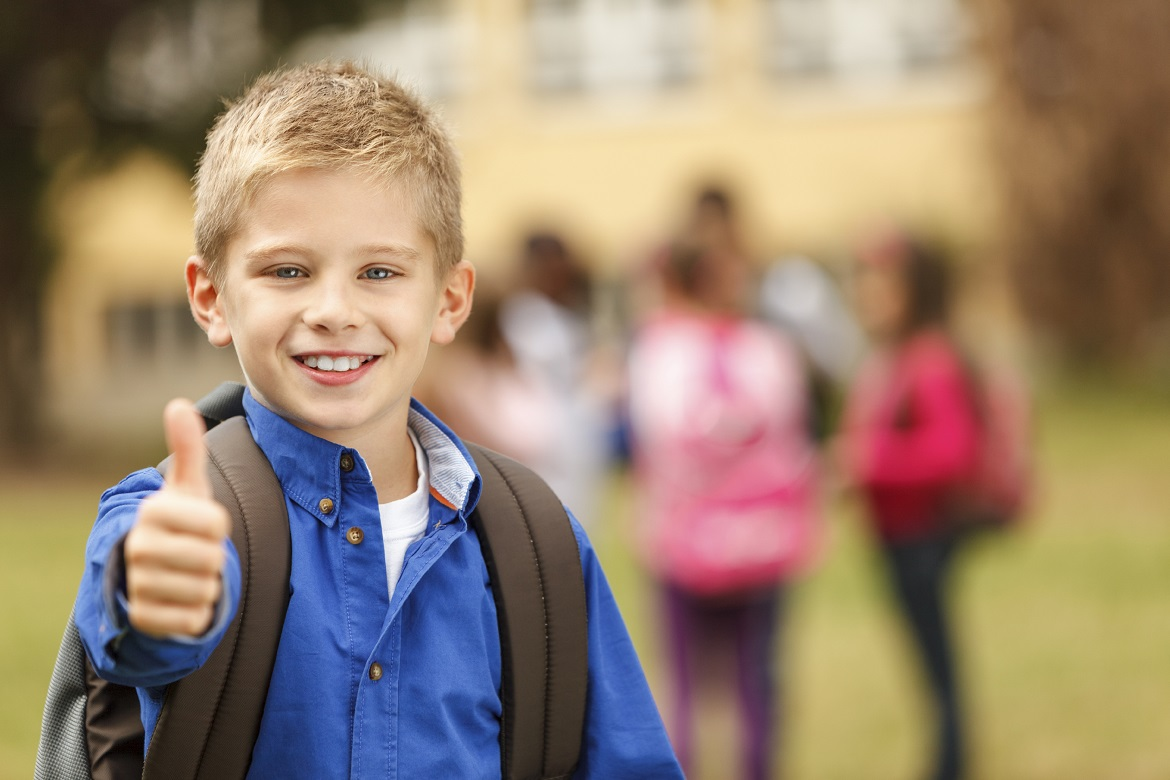 Schoolboy in front of the school showing thumb-up